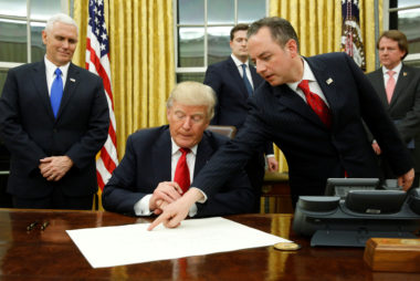 Priebus directs Trump where to sign the document confirming James Mattis his Secretary of Defense, his first signing in the Oval Office in Washington