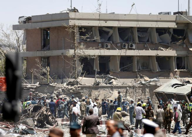 Afghan officials inspect outside the German embassy after a blast in Kabul, Afghanistan