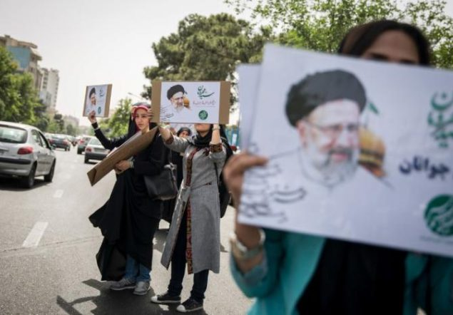 Supporters of Iranian Presidential candidate Ebrahim Raisi hold his posters outside the Mosalla mosque in Tehran
