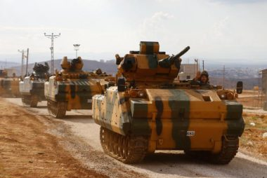Turkish military convoy drives by village on Turkish-Syrian border line in Reyhanli