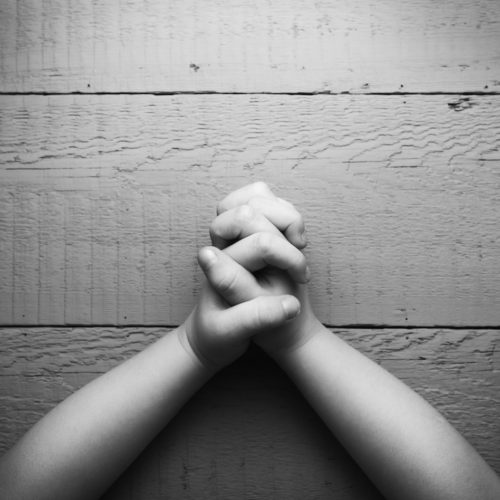 Child's hands folded together in prayer. Black and white photo