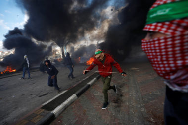 Image: Palestinian protesters run during clashes with Israeli troops at a protest against U.S. President Donald Trump's decision to recognize Jerusalem as the capital of Israel, near the Jewish settlement of Beit El, near the West Bank city of Ramallah