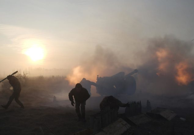 Ukrainian servicemen fire an artillery weapon near Novoluhanske in Donetsk region