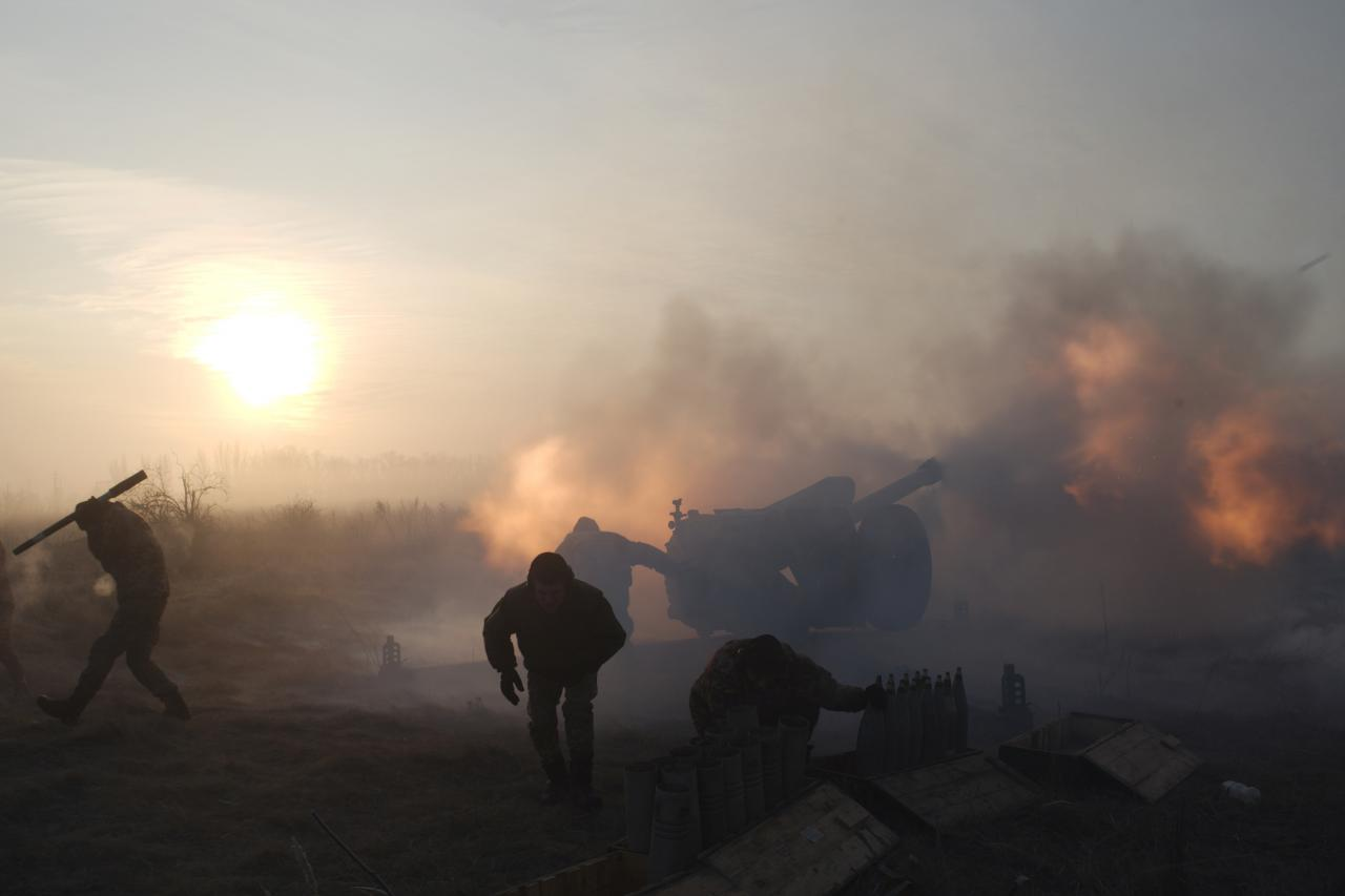 Ukrainian servicemen fire an artillery weapon near Novoluhanske in Donetsk region