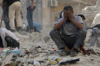 A man reacts amid debris after what activists said were explosive barrels thrown by forces loyal to Syria's President Assad in Al-Shaar neighbourhood of Aleppo