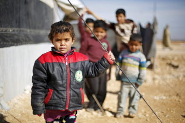 Syrian refugee children pose as they play near their families' residence at Al Zaatari refugee camp in Mafraq
