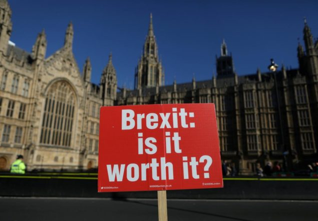 An anti-Brexit placard is fixed to traffic barriers opposite the Houses of Parliament in London