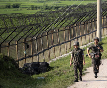 FILE - In this June 30, 2014 file photo, South Korean army soldiers patrol through the military wire fence in Paju, near the border with North Korea, South Korea.  Border guards of the rival Koreas exchanged gunfire Sunday, Oct. 19, 2014,  along their heavily fortified border in the second such shootout in less than 10 days, South Korean officials said.  (AP Photo/Ahn Young-joon, File)