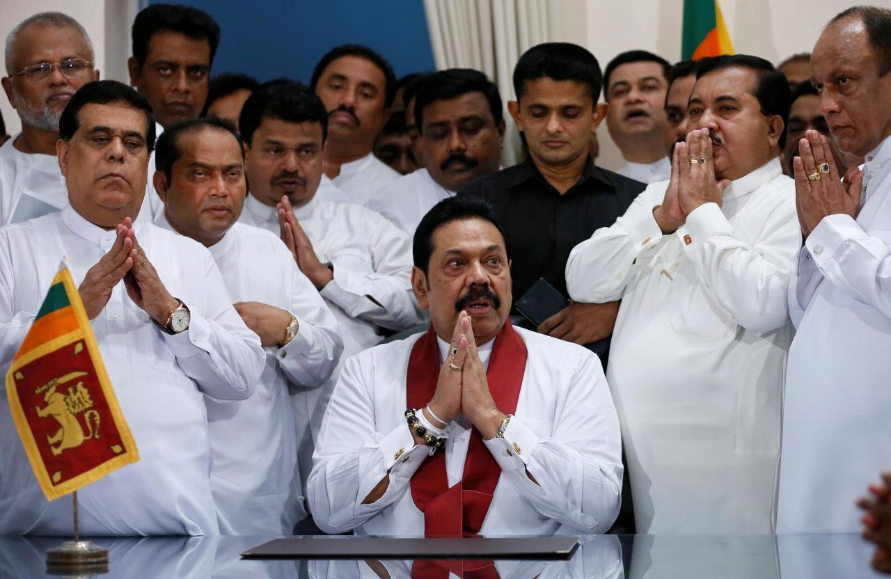 Sri Lanka's newly appointed Prime Minister Rajapaksa gestures with his party members during the ceremony to assume duties at the Prime Minister office in Colombo