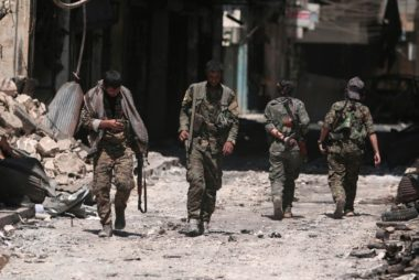 FILE PHOTO: SDF fighters walk on the rubble of damaged shops and buildings in Manbij