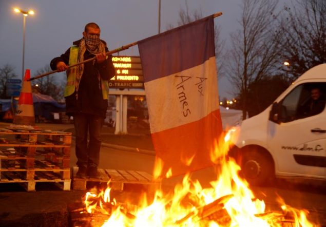 A protester wearing a yellow vest, the symbol of a French drivers' protest against higher fuel prices, holds a flag at the approach to the A2 Paris-Brussels Motorway, in Fontaine-Notre-Dame
