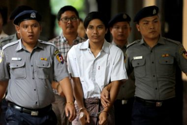 FILE PHOTO: Detained Reuters journalists Kyaw Soe Oo and Wa Lone are escorted by police as they arrive before a court hearing in Yangon