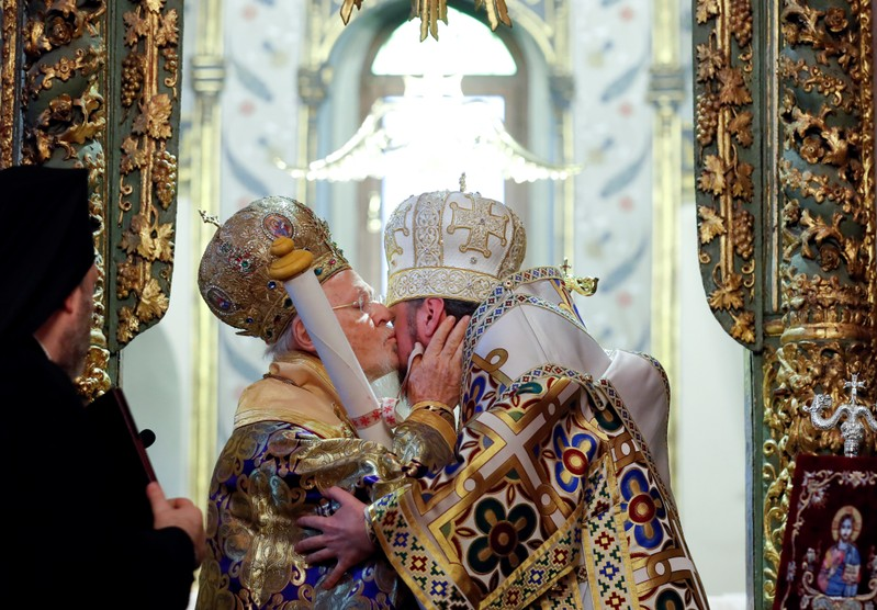 Ecumenical Patriarch Bartholomew I kisses Metropolitan Epifaniy as he hands Tomos after the Epiphany mass at the Patriarchal Cathedral of St. George in Istanbul