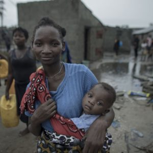 """17 March 2019. (wearing blue with baby in sling)Enia Joao, 24, has 3 children. The youngest  one being 10months old on back. She is from the community.1:34 sec - 1:38""""In all my life I have never see such a storm like this."""" Praia Nova Village was one of the most affected neighborhoods in Beira. Being a located on the coast, this shanty town of loosely built homes were extremely vulnerable to the high winds and rain. Following the cyclone families are returning trying to pick up the pieces of their lives.  Photo by  Josh Estey/CARE"""