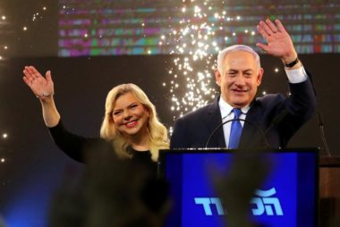 Israeli Prime Minister Benjamin Netanyahu and his wife Sara wave as Netanyahu speaks following the announcement of exit polls in Israel's parliamentary election at the party headquarters in Tel Aviv, Israel