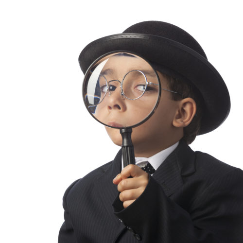 Little detective looking through magnifying glass