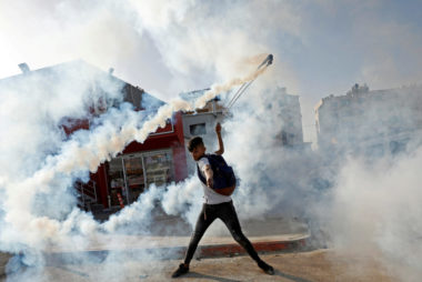 Demonstrator returns a tear gas canister during a protest as Palestinians call for a day of rage in the Israeli-occupied West Bank