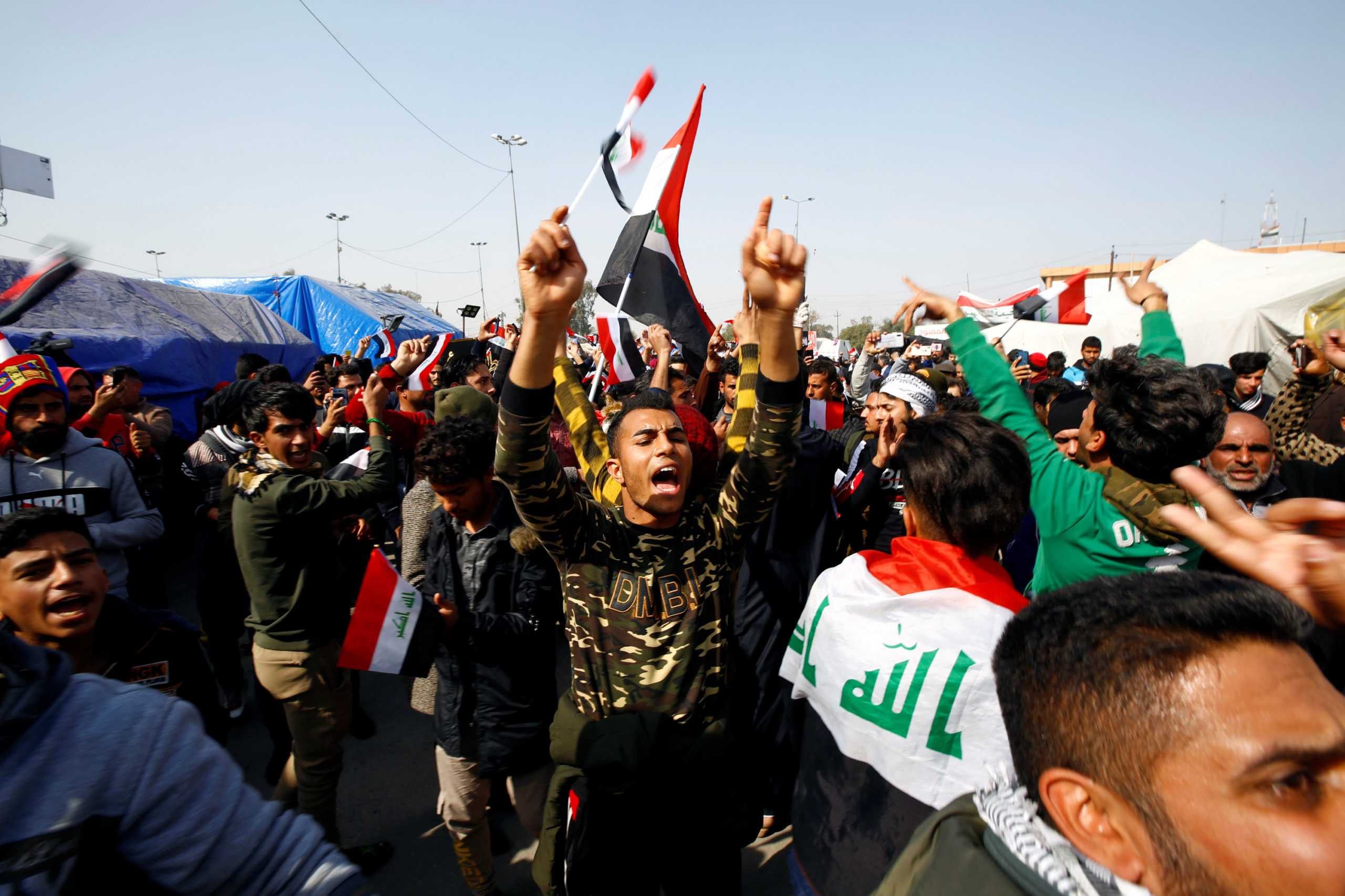 Iraqi demonstrators chant slogans during ongoing anti-government protests in Najaf