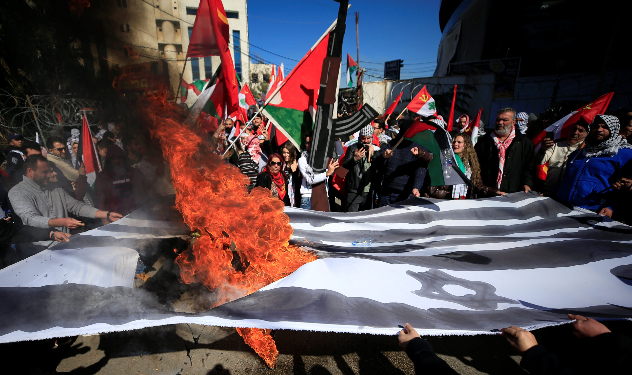 Demonstrators set fire to a makeshift Israeli and U.S. flag during a protest against the U.S. President Donald Trump's Middle East peace near the U.S. embassy in Awkar
